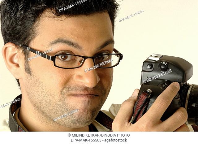 Photographer using still SLR camera strap around neck MR748L