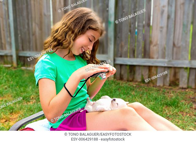 Kid girl taking photos to puppy dog pet with camera in outdoor backyard
