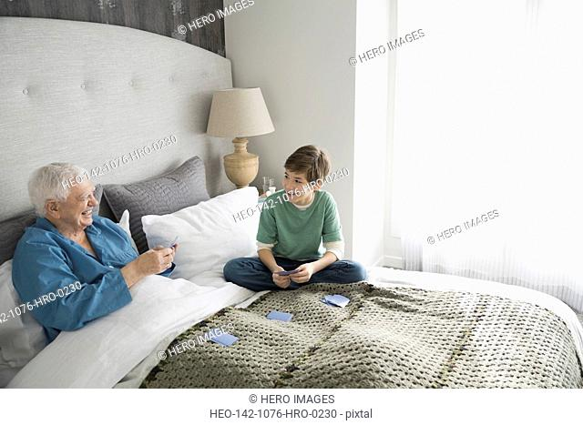Happy grandfather and grandson playing cards in bedroom