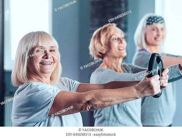Active retired life. Selective focus on a beaming retired woman looking into the camera while taking an exercise class and lifting a weight disk