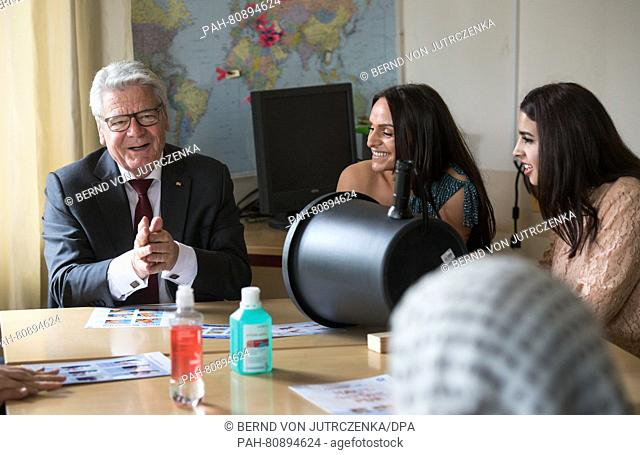 German President Joachim Gauck (L) listens as Belkisa Samardzic (C) and Amal El-Awad (R) explain hand sanitation to him at a class for care assitants at the...