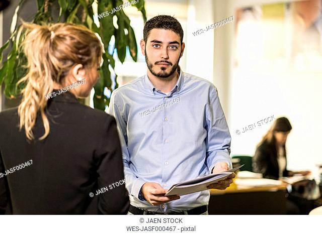 Portait of man with woman in office holding documents
