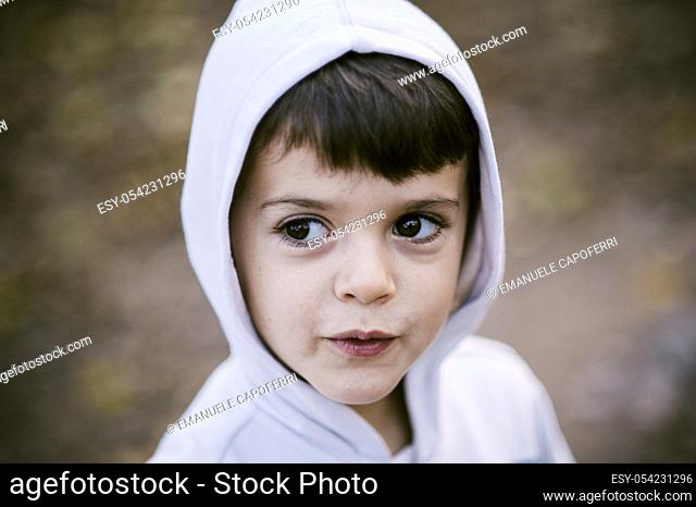 Portrait of baby with plush white in an avenue of trees in autumn