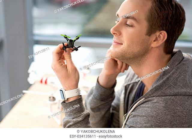 This is the best toy for a spy. Portrait of attractive man holding a small quadrocopter and looking at it with satisfaction