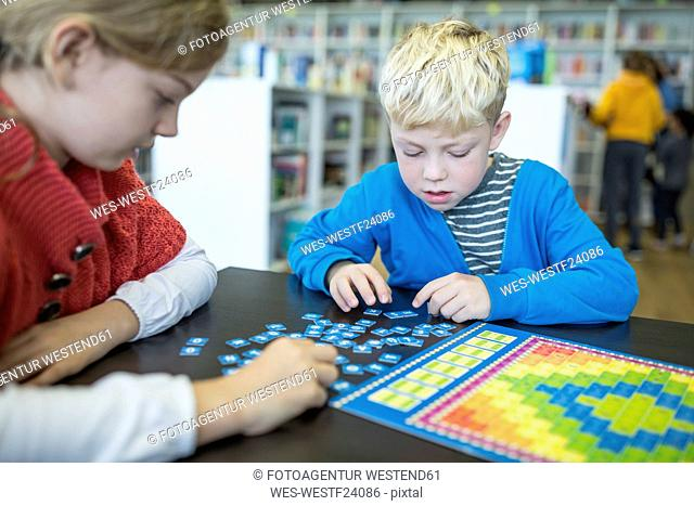 Pupils playing a board game in school library
