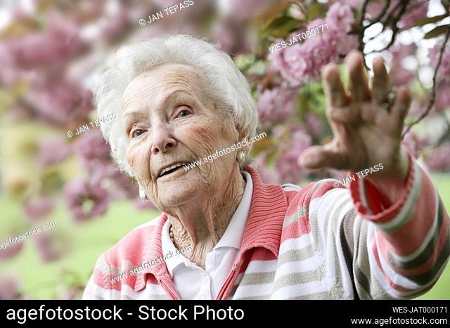 Germany, North Rhine Westphalia, Cologne, Senior woman in park, looking away