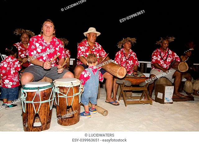 Portrait of Polynesian Pacific Island Tahitian music group in colorful outfit in play music on tropical beach