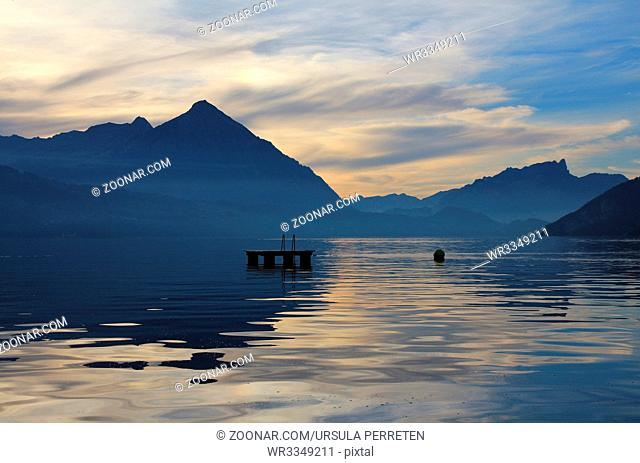 Summer scene in the Swiss Alps. Lake Thunsersee and mount Niesen