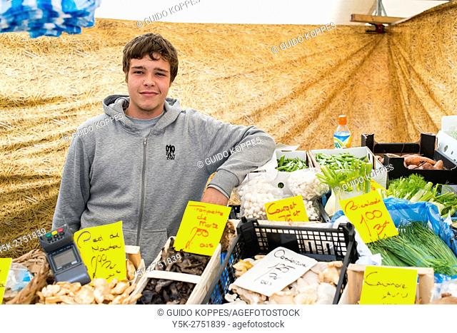 Rotterdam, Netherlands. Young teenage guy selling groceries from his father's market stall at Blaak Square