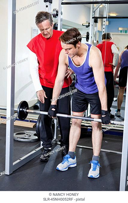 Man lifting weights with trainer in gym