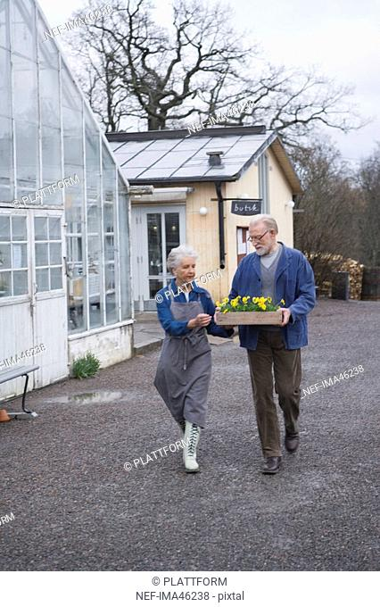 An older couple holding a flower box outside a greenhouse Sweden