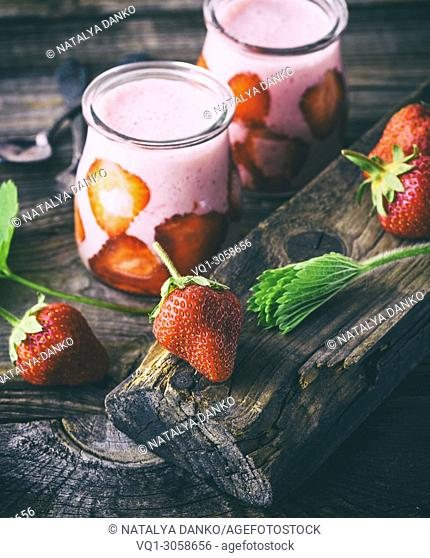 ripe red strawberry and two glass jars of smoothies on a gray wooden table