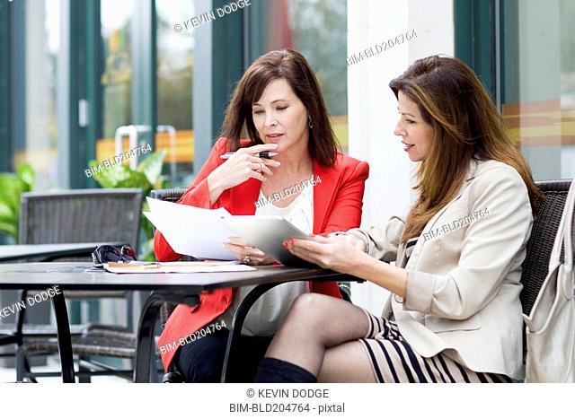 Caucasian businesswomen working at cafe