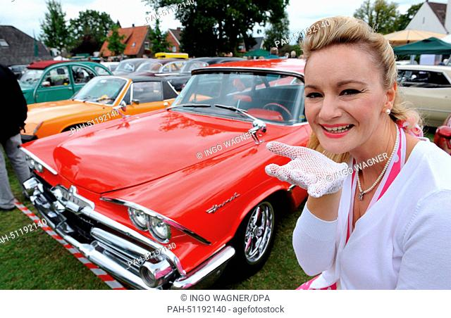 Sonja in a 50s dress presents the US car Dodge Coronet from 1959 at the 8th vintage car meeting for cars and motorcycles in Rastede, Germany, 17 August 2014