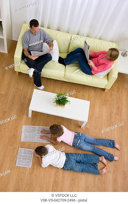 USA, Illinois, Metamora, Family reading newspapers in living room