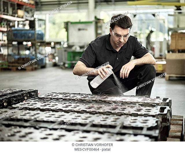 Worker in metalworking factory spraying on cylinder head