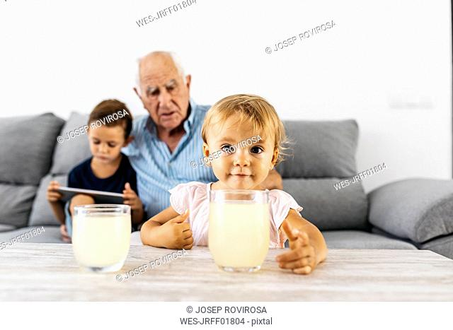 Portrait of little girl with glass of lemonade at home with brother and grandfather in the background