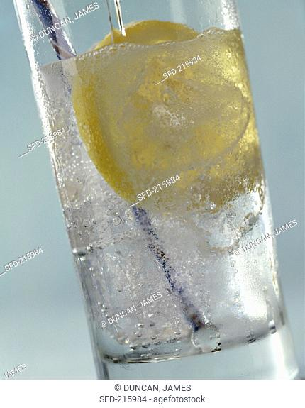 A Glass of Water with Lemon Slice and Straw