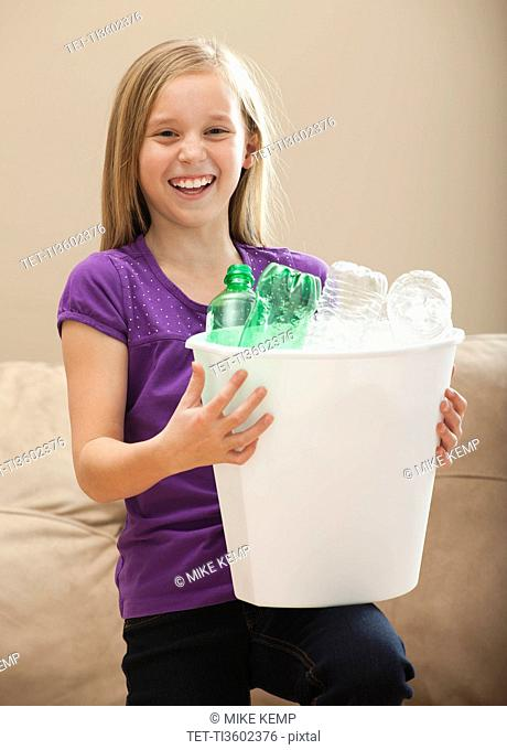 USA, Utah, Lehi, Portrait of girl 8-9 holding recycling bin with plastic bottles
