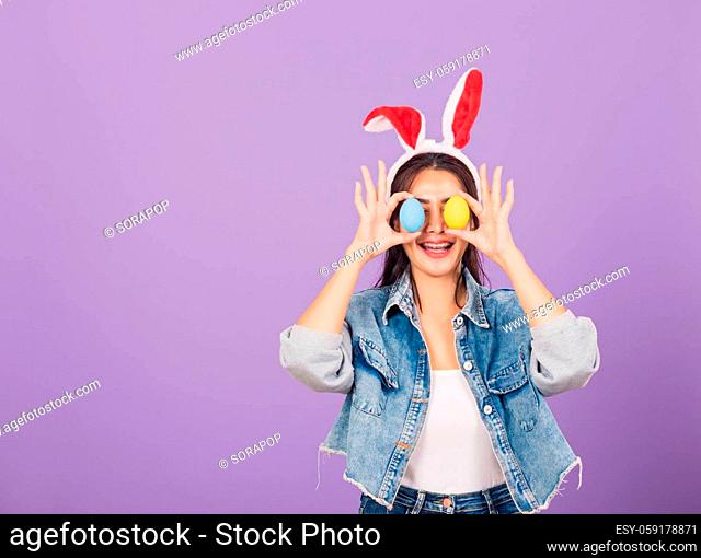 Happy beautiful young woman smiling wearing rabbit ears and denims holding colorful Easter eggs front eyes, Thai female with bunny ear, easter egg cover eye