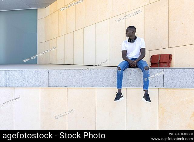 Thoughtful man sitting by bag on wall