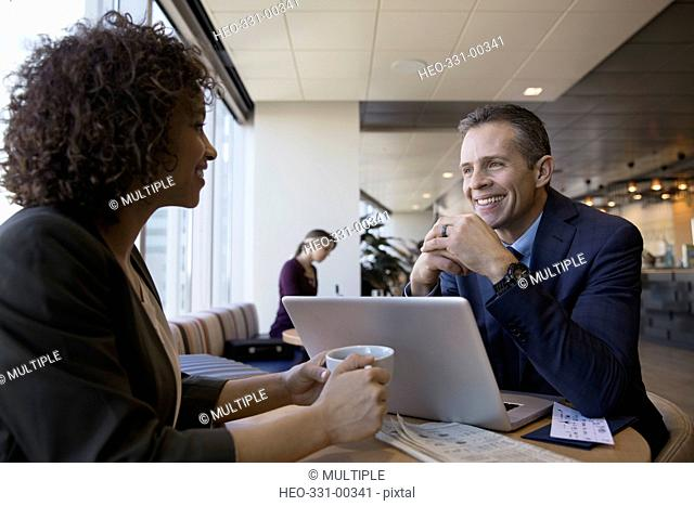 Smiling business people using laptop and drinking coffee in airport lounge