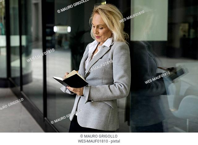Senior businesswoman leaning against glass front checking diary