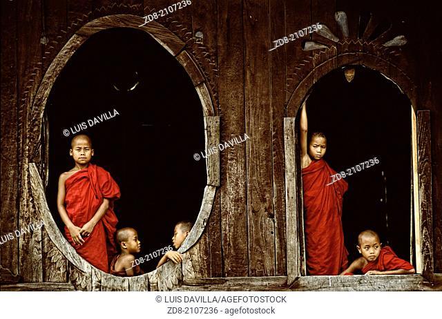 Monks in the windows of a teak monastery .Myanmar