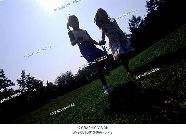 Low angle view of two young girls running holding hands