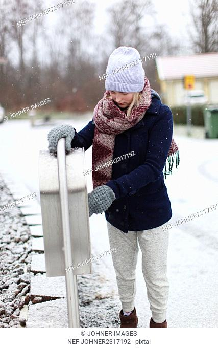 Woman standing by mailbox