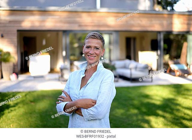 Portrait of smiling woman standing in garden of her hpuso