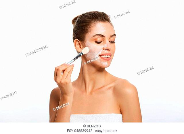 Portrait beautiful naked woman apply cosmetic white clay mask on with brush. Isolated on a white background. concept of beauty and health