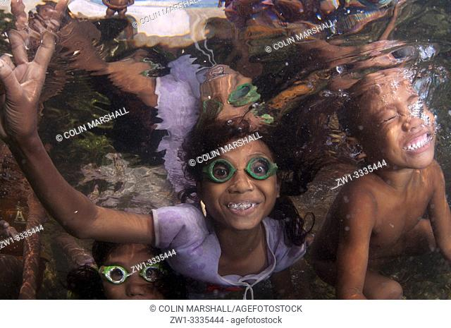 Kids with goggles underwater and making hand signals, Pier, Reta Island, Alor, Indonesia