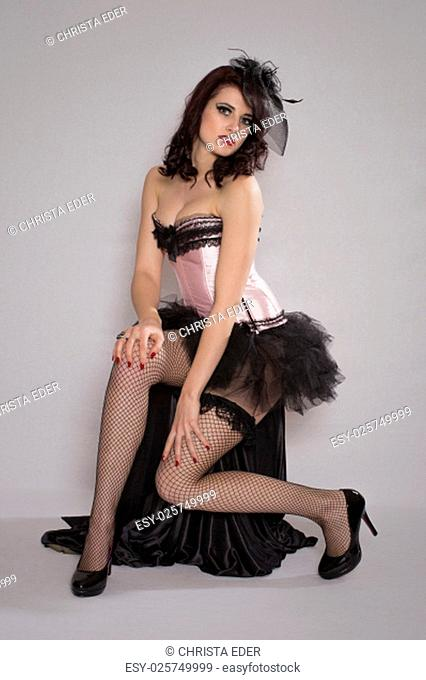 pretty erotic young woman in burlesquestil sitting on a stool