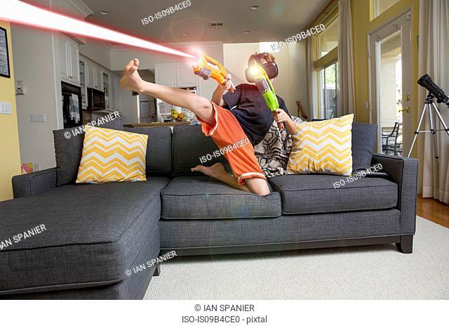 Young boy on sofa, wearing virtual reality headset, kicking leg, firing laser guns, digital composite