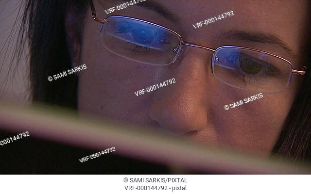 Woman working on computer, reflection in spectacles, close-up