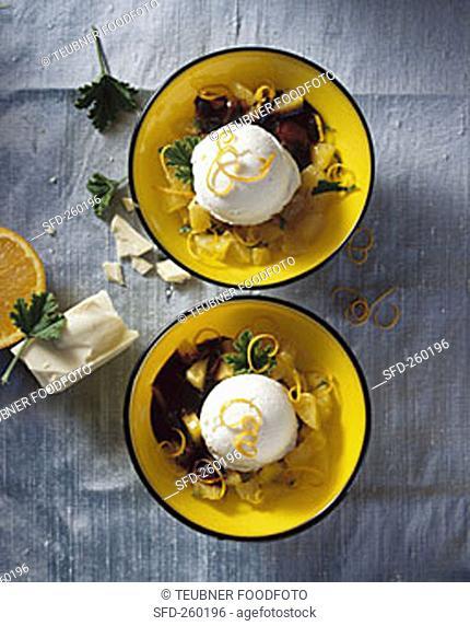 Soya yoghurt ice cream on oranges with scented geranium leaves