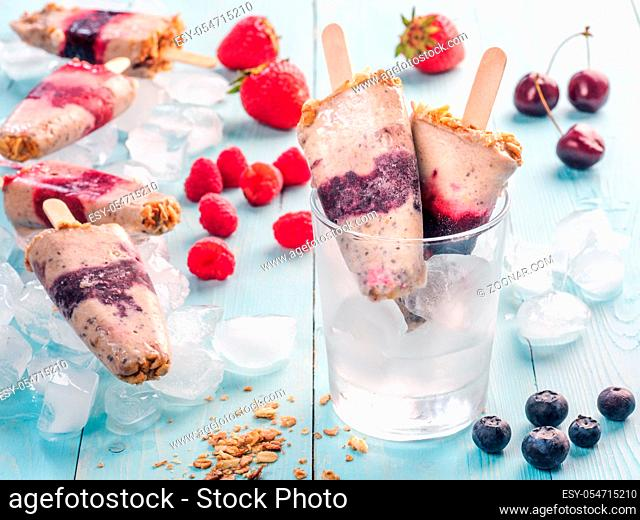Homemade popsicle and cherry, blueberry, strawberry, raspberry on blue wooden background. Healthy summer breakfast. Popsicles from yogurt and banana with...
