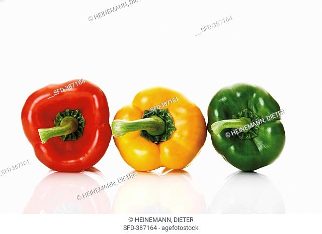 A red, a yellow and a green pepper side by side