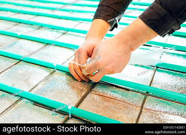 underfloor heating installation, pipes fastening with tie wraps by hands