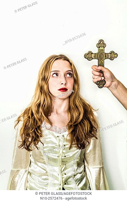 Woman's hand holding a cross next to a blonde teenage girl