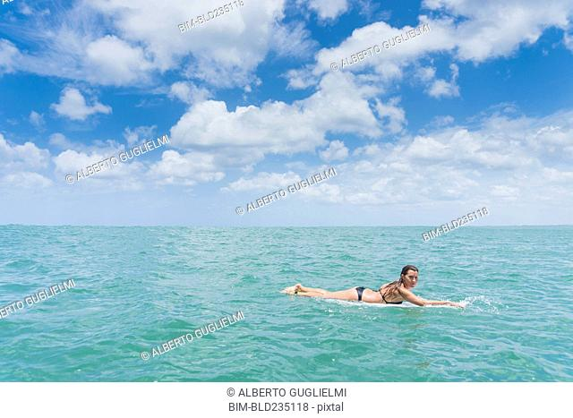 Caucasian woman paddling on surfboard in ocean