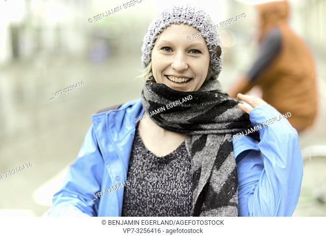 happy optimistic woman with scarf outdoors in bad weather, in Munich, Germany