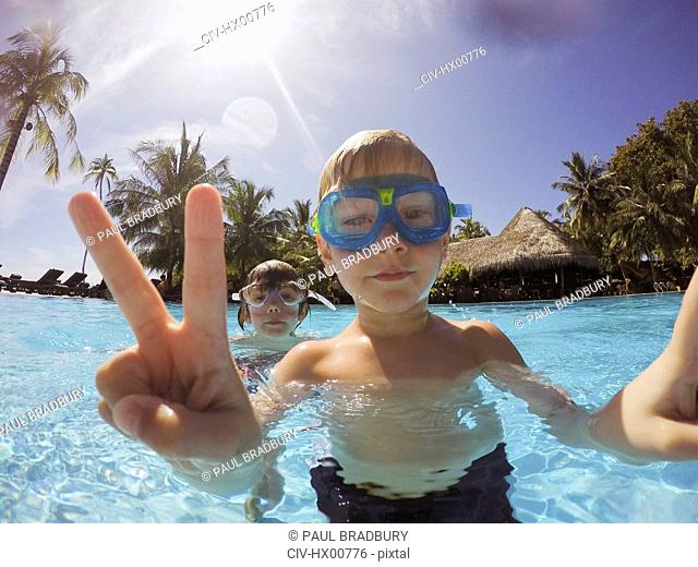 Portrait of boy gesturing peace sign in tropical swimming pool