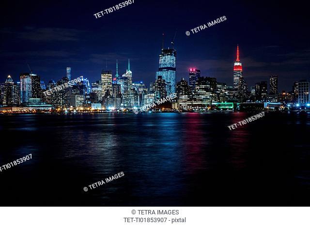 Illuminated cityscape reflecting in river