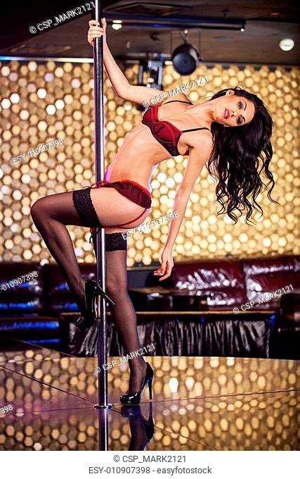 Sexy pose of beautiful pole dancer. Turning around the pole over golden background