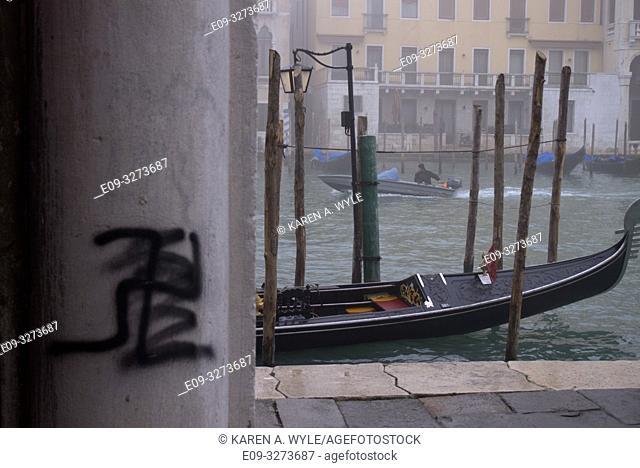 graffiti swastika, with scribble under or over it, on pillar near Rialto Fish Market, Venice, Italy