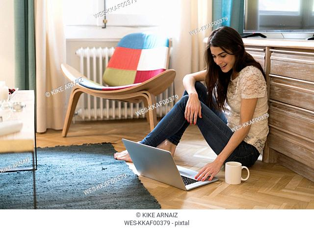 Young woman sitting on the floor at home using laptop