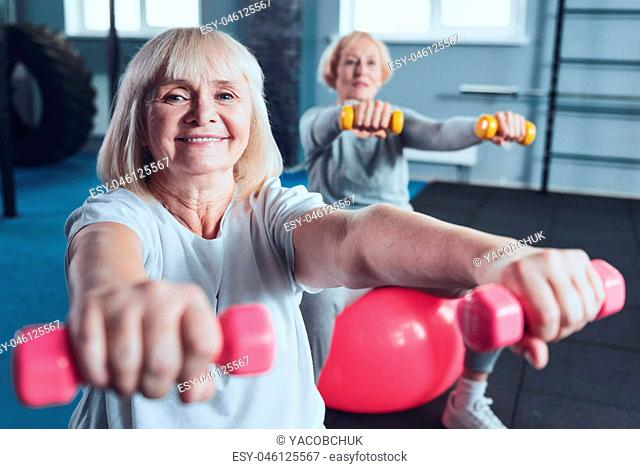 Total joy. Selective focus on a beaming mature lady looking into the camera while exercising with dumbbells on a fitness ball at a gym