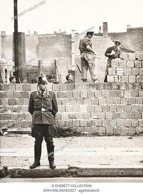 West Berlin policeman stands before the concrete block wall dividing East and West Berlin. Along Bernauer Strasse, East Berlin workmen add blocks to increase...